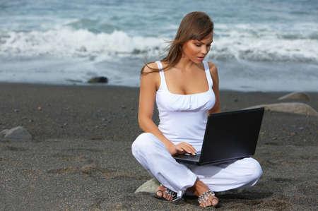 Beautiful woman on the beach working on laptop photo