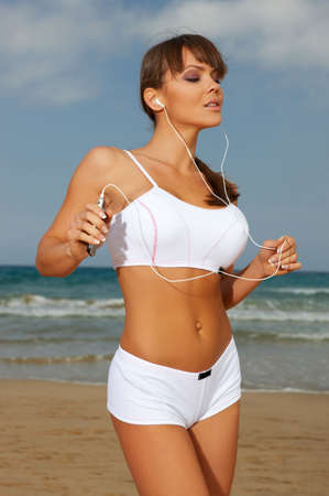 radio activity: Beautiful woman during fitness on sea beach is listen to the music Stock Photo