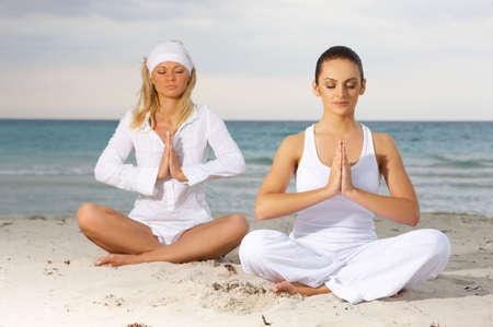 cuba girl: Two Young beautiful women during yoga on sea beach  Stock Photo