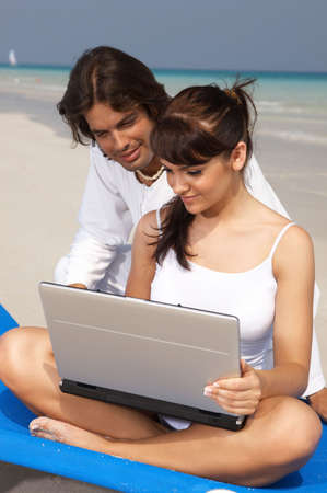 young couple working on laptop computer at the beach photo