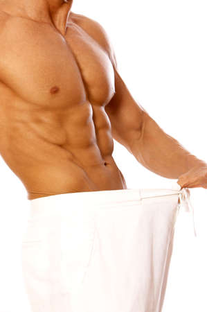 Muscular and tanned male in old pants after weight loss