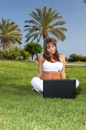 Young beautiful woman sitting on grass and using laptop  photo