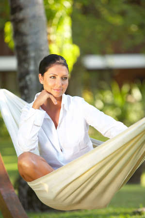 20-25 years woman portrait ralaxing on hammock at exotic surrounding