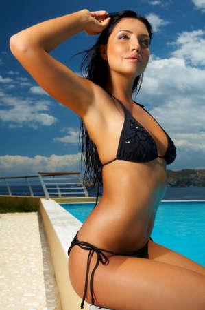 Beautiful young Sexy woman standing in black bikini next to swimming pool Stock Photo
