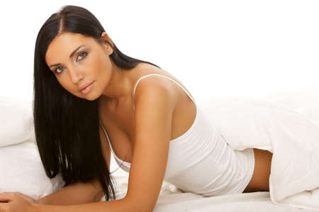 Portrait of 20-25 years old beautiful woman on white bed photo