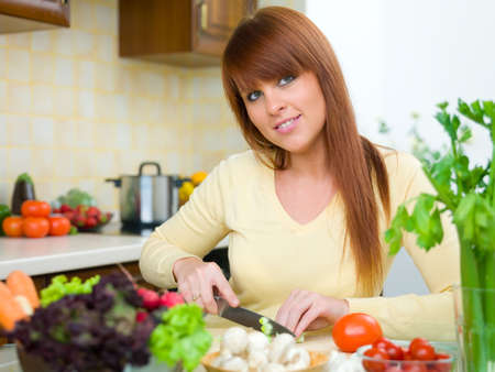 Beautiful woman in kitchen cooking meal