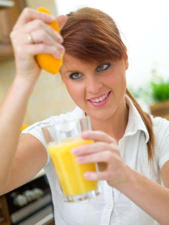 squeezed: Mujer hermosa en la cocina de naranja a apretar vidrio