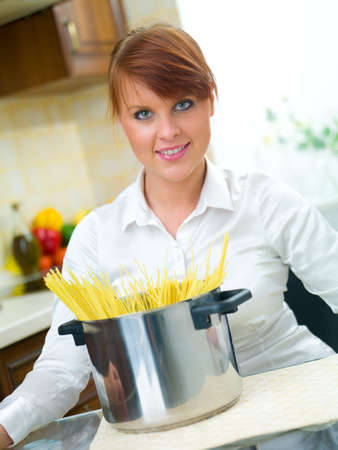 Beautiful woman in kitchen is preparing spaghetti photo