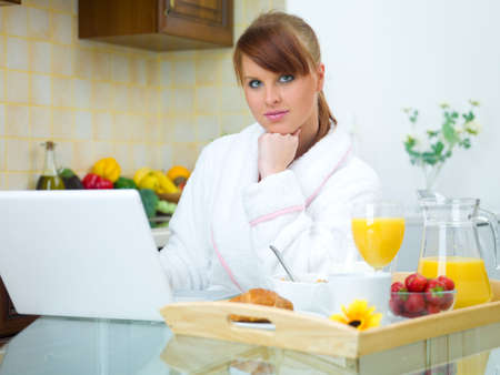 Beautiful woman in kitchen eating tasty breakfast photo