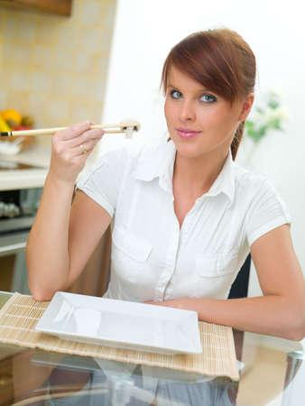 Beautiful woman in kitchen eating using chopsticks photo