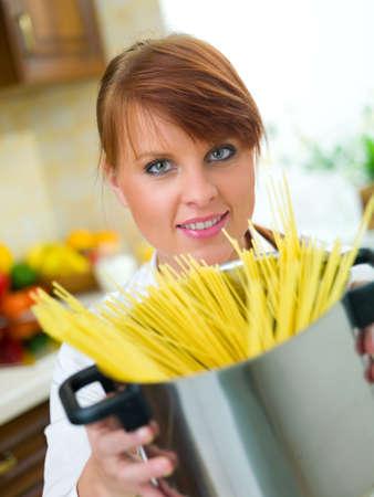 Beautiful woman in kitchen is preparing spaghetti photo
