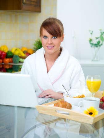 Beautiful woman in kitchen eating tasty breakfast photo