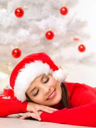 Beautiful woman next to christmas tree wearing red sweater photo