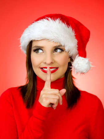 artificial hair: Portrait of beautiful woman wearing santa claus hat on red background