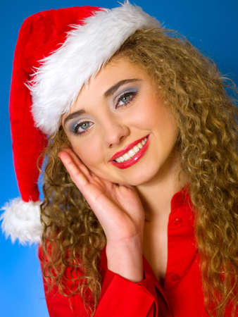 Portrait of beautiful woman wearing santa claus hat on blue background photo