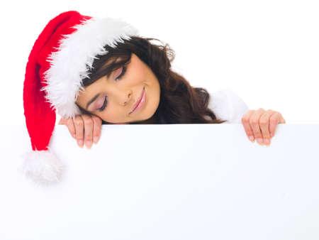Beautiful christmas woman in santa hat holding empty board photo