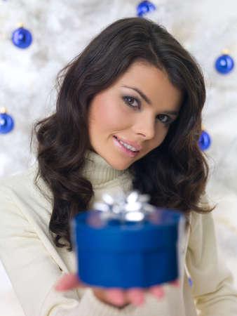 Beautiful woman next to christmas tree on white  photo