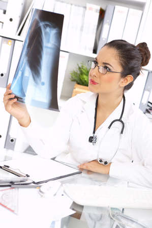 Portrait of female doctor examining x-ray picture photo