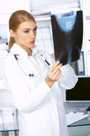 Female doctor examining x-ray picture and is worried photo