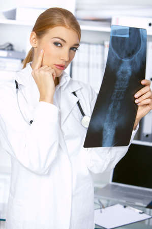 Thinking female doctor and examining x-ray picture photo
