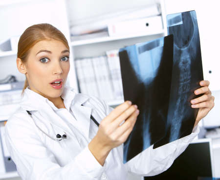 Portrait of confused female doctor examining x-ray picture photo