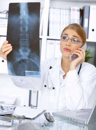 Portrait of female doctor examining x-ray picture and talking cell photo
