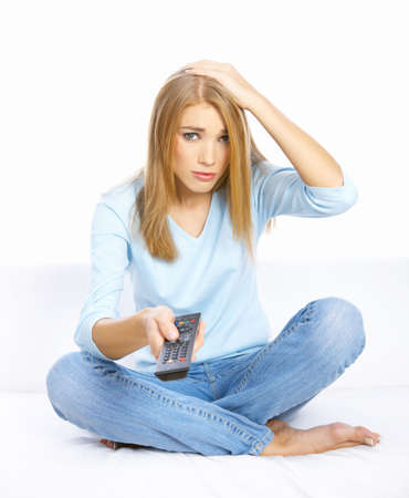 tv remote: Confused woman sitting on couch with tv remote controler