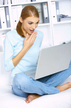Shocked woman sitting on couch and working on laptop photo