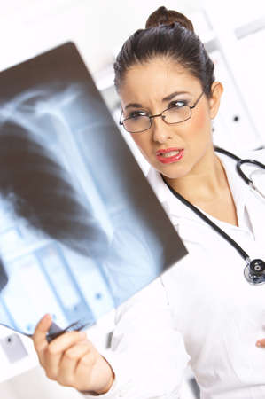 Very worried female doctor examining x-ray picture Stock Photo - 3952306