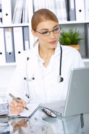 Smiling female doctor writing notes in clipboard photo