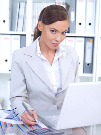 Business woman working in office, looking at camera and smiling photo
