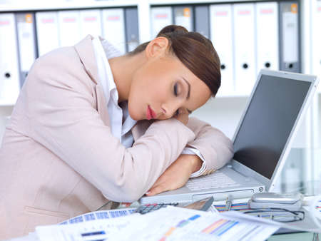 Beautiful business woman laying on desk and sleeping photo