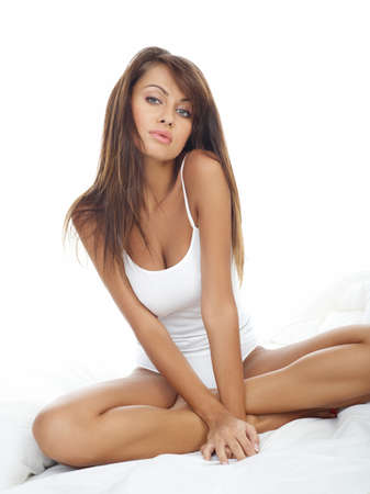 Portrait of beautiful woman, she sitting on white bed