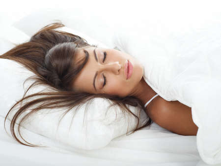 coverlet: Portrait of beautiful woman in white bed Stock Photo