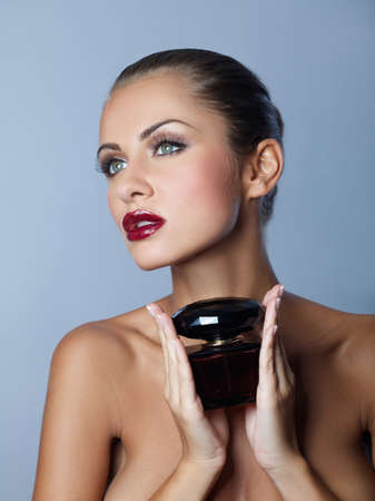 Portrait of beautiful brunette and sexy woman with perfume photo