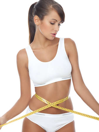 fatness: Young beautiful woman with measure tape on white