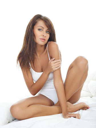 coverlet: Portrait of beautiful woman, she sitting on white bed