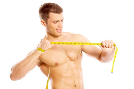 body built: Muscular and tanned man ripping measire tape Stock Photo