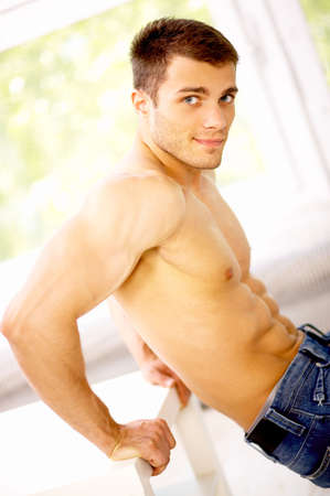 body built: Muscular and tanned male is excersing, wearing jeans Stock Photo
