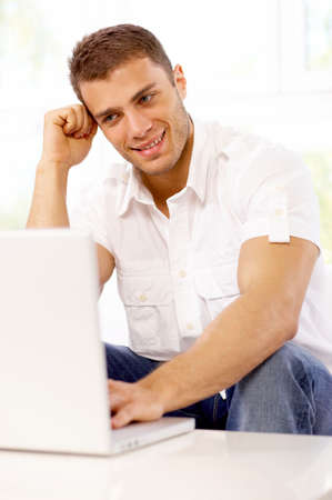 Young man sitting on couch and working on laptop Stock Photo - 4752635