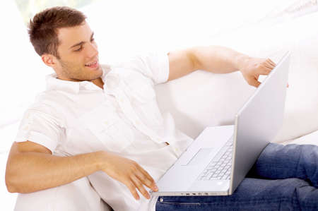 Young man sitting on couch and working on laptop Stock Photo - 4752655