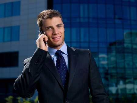 Portrait of business man outside the building using cell phone photo