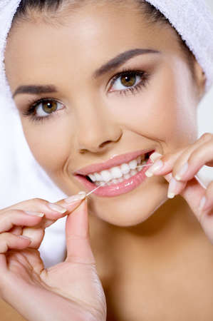 dental care: Portrait of beautiful woman with dental floss
