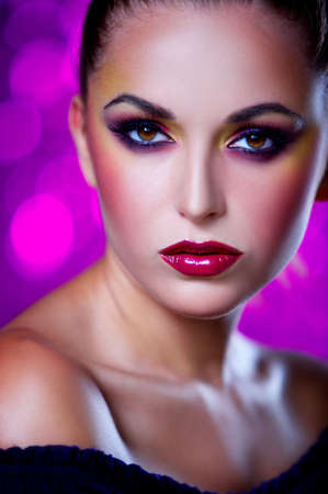 Portrait of beautiful young sexy woman on crimson background photo