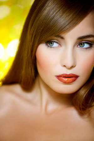 Portrait of beautiful young sexy woman on yellow background photo