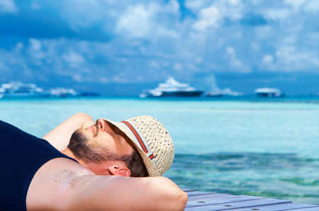 Handsome man resting near water at Maldives photo