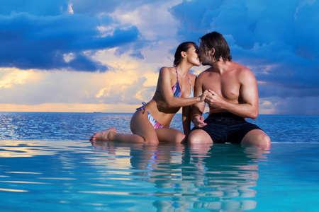 copule: Romantic couple sitting next to swimming pool Stock Photo