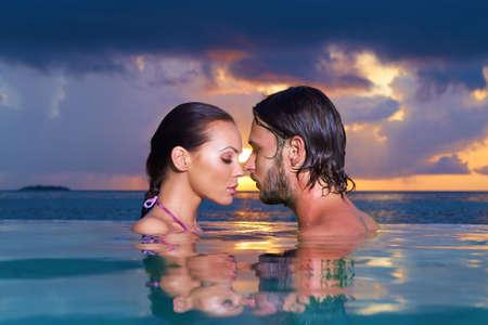 copule: Romantic couple alone in infinity swimming pool