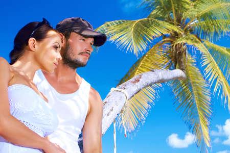 Romantic couple standing next to palm tree Stock Photo - 6878974