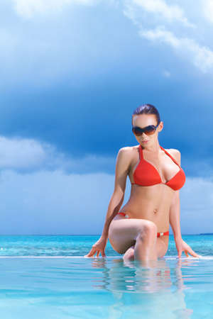 Beautiful woman resting near pool at Maldives